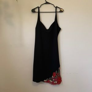 Black sheath dress with red floral lace appliqué